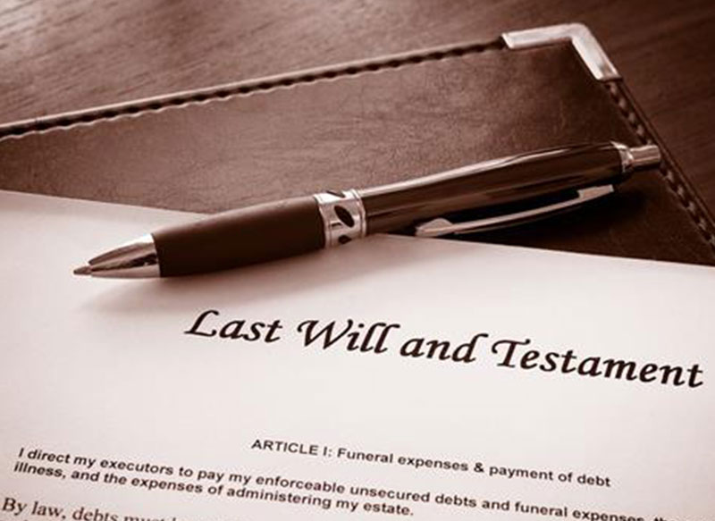 Last Will and Testament document sitting on leather folder with pen
