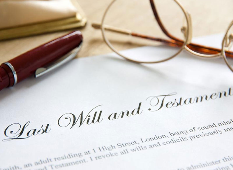 Last Will and Testament document on table with pen and glasses